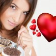 Smiling brunette woman eating some cake in the living room in her apartment. Graphic 3d red heart symbols are flying near her. She is in love — Stock Photo