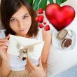 Young pretty attractive smiling woman with heart lying relaxed at her home on sofa. Top View - Foto de Stock