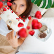 Portrait of young pretty woman eating tasty cakes on Valentines Day and graphic hearts are flying around her — Stock Photo #9248474
