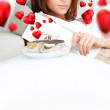 Portrait of young pretty woman eating tasty cakes on Valentines Day and graphic hearts are flying around her - Stock fotografie