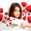 Portrait of young pretty woman eating tasty cakes on Valentines Day and graphic hearts are flying around her — Stock Photo #9248488