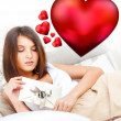Cute young woman holds a valentine and reading it. Beautiful heart symbols flying around her. She is in love with her couple — Stock Photo #9248494