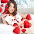 Cute young woman holds a valentine and reading it. Beautiful heart symbols flying around her. She is in love with her couple - 图库照片