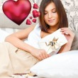 Portrait of young pretty woman lying on soft comfortable sofa and reading her valentine card with pleasure. Graphic 3d red heart symbols are floating around her. She is thinking about her couple — Stock Photo