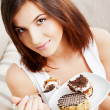 Young beautiful woman with a cake. Close-up portrait. Sitting on sofa at her home — Stock Photo