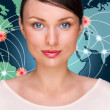 Attractive brunette young woman in futuristic interface standing in front of world map with glowing hot points location and connection lines - Stock Photo