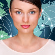 Attractive brunette young woman in futuristic interface standing in front of world map with glowing hot points location and connection lines — Stock Photo #9248833
