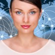 Portrait of young pretty woman looking at camera and standing in front of world map with glowing connection lines and server location points. Global Internet communications technology — Stockfoto
