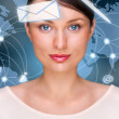A business woman with icons of her affairs floating around her head. Portrait of pretty girl working with her virtual pc looking at camera and smiling. Daily deals online. World map at the back — Stock Photo