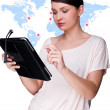 Portrait of young woman standing in front of big world map and looking at her tablet computer — Stock Photo
