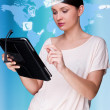 A business woman with icons of her affairs floating around her head. Portrait of pretty woman working with her tablet pc looking at screen and smiling. Daily affairs online — Stock Photo #9248917