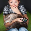 Young funny woman sitting in her beanbag and embracing her cat while watching tv. She is very scared while watching horror film in dark room — Stock Photo #9249024