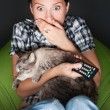 Young funny woman sitting in her beanbag and embracing her cat while watching tv. She is very scared while watching horror film in dark room — Stock Photo