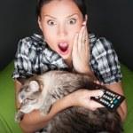 giovane donna divertente seduta nella sua poltrona sacco e abbracciando il suo gatto mentre si guarda la tv. Lei è molto spaventata guardando film horror in camera oscura — Foto Stock