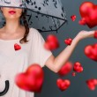 Young fashionable woman holding umbrella standing against grey background red hearts are floating around her. Love rain concept — Stock Photo