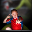 Close-up portrait of young man wearing sportswear fan of football team is watching tv and rooting for his favorite team. Sitting on beanbag alone at night. Light from television — Stock Photo