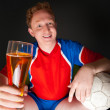 Young man holding soccer ball and beer and watching tv translating of game at home wearing sportswear - Stock Photo