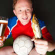 Foto Stock: Young mholding soccer ball, beer and stockfish, watching tv translating of game at home wearing sportswear