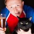 Portrait of young man holding a glass of beer and a big black cat and both looking at camera while watching tv translation of their favorite football team — Stock Photo