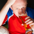 Young man holding soccer ball and beer and watching tv translating of game at home wearing sportswear — Stock Photo