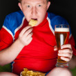 Close-up portrait of young man wearing sportswear fan of football team is watching tv and rooting for his favorite team. Sitting on beanbag alone at night drinking beer and eating chips - Stock Photo