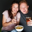 Happy couple sitting together watching something interesting on television drinking and eating - Grey background — Stock Photo