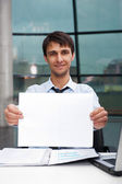 Attractive man in business suit with blank sign sitting at his office and smiling to camera — Stock Photo