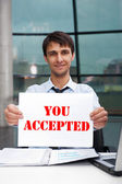 Attractive man in business suit with acceptance sign sitting at his office and smiling to camera — Stock Photo