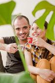 Atraktivní mladý dospělý pár sedící blízko na dřevěnou podlahu v domácí usmívá, pití nápojů a směje se. monstera rostlin na popředí v rozostření — Stock fotografie