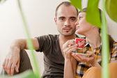 Séduisante jeune couple adulte assis à proximité sur le plancher de bois franc dans l'accueil souriant, boire des boissons chaudes et le rire. monstera plante sur l'avant-plan dans le flou — Photo