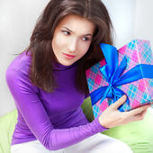 Delighted woman opening a gift sitting on the bean bag at home. Valentine day concept poster — Stock Photo