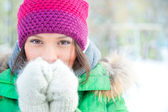 Winter woman in snow looking at camera outside on snowing cold winter day. Portrait caucasian female model outside in first snow — Stock Photo