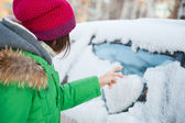 Beautiful woman in winter clothes drawing heart on car — Stock Photo