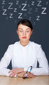 Bored businesspeople: woman sitting at desk with closed eyes. Young caucasian business woman at her office — Stock Photo