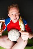 Młody człowiek posiadania piłki nożnej, piwo i sztokfisz, oglądanie tv tłumaczenie gry w domu noszenie odzieży sportowej — Zdjęcie stockowe