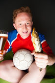Young man holding soccer ball, beer and stockfish, watching tv translating of game at home wearing sportswear — Stok fotoğraf