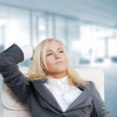 Happy businesswoman in the office resting and daydreaming — Stok fotoğraf