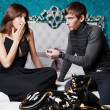 Stock Photo: Fashion style photo of an attractive young couple inside luxury aristocratic interior of their apartment. Man making proposal to his girlfriend and giving a ring to her