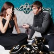 Fashion style photo of an attractive young couple inside luxury aristocratic interior of their apartment. Man making proposal to his girlfriend and giving a ring to her — Stock Photo