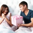 Close-up portrait of a happy young couple relaxing on the bed. Man making a gift to his girlfriend. Saint Valentine concept — Stock Photo
