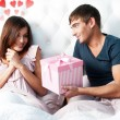 Close-up portrait of a happy young couple relaxing on the bed. Man making a gift to his girlfriend. Saint Valentine concept. Graphic heart — Stock Photo