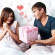 Close-up portrait of a happy young couple relaxing on the bed. Man making a gift to his girlfriend. Saint Valentine concept. Graphic heart — Stock Photo #9250310