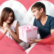Portrait of happy couple lying in the bed. Girl feeding her boyfriend with spoon of tasty cake. Beautiful graphic red hearts are flying around — Stock Photo