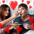 Royalty-Free Stock Photo: Portrait of happy couple lying in the bed. Girl feeding her boyfriend with spoon of tasty cake. Beautiful graphic red hearts are flying around