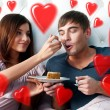 Portrait of happy couple lying in the bed. Girl feeding her boyfriend with spoon of tasty cake. Beautiful graphic red hearts are flying around - Stock Photo
