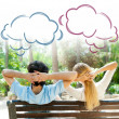 Foto Stock: Smiling beautiful couple sitting on a bench at summer park and dreaming about something