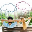 Smiling beautiful couple sitting on a bench at summer park and dreaming about something — Stockfoto #9250688