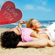 Young beautiful romantic couple relaxing on beach at sunny day. Heart and sign i love you — Stock Photo