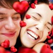 Close-up of young couple embracing and very happy to be together. Valentine concept. Red hearts are flying around them — Stock Photo