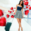 Young woman with luggage at the international airport. She is flying to her couple. Red Hearts are flying around her — Stock Photo #9254398